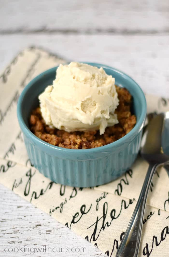 Rhubarb Crisp topped with vanilla ice cream in a small blue bowl sitting on a French script napkin with a spoon on the side