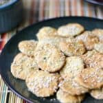 Sesame Crackers on a dark plate sitting on a rainbow colored place mat