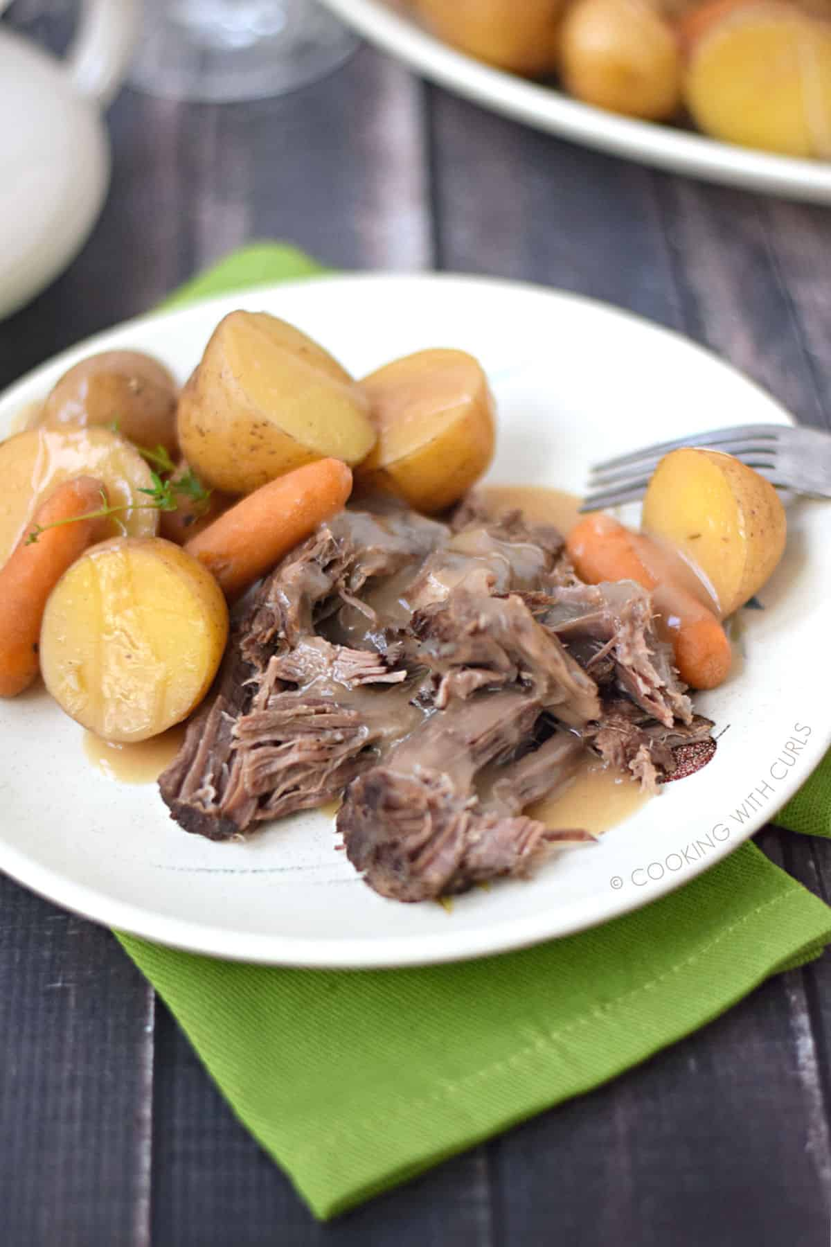 pot roast with sliced potatoes and baby carrots topped with beef gravy on a white plate that is sitting on a green napkin.
