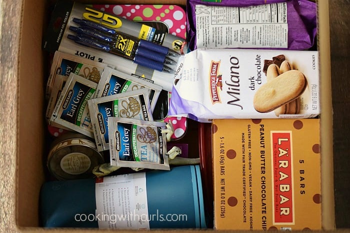 box filled with cookies, teas, pens and snack bars