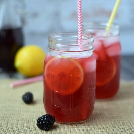 Blackberry Passion Tea Lemonade in glass mason jars with colorful paper straws and a lemon in the background