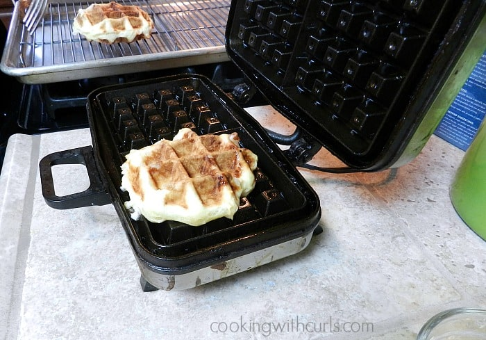 Two golden brown Liege waffles. One of a wire cooling rack and the other in the waffle iron.
