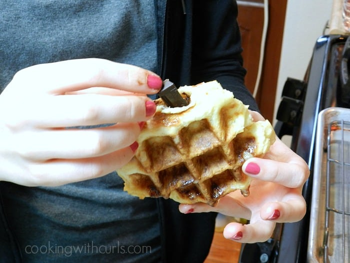 A girl holding a cooked waffle while stuffing a strip of chocolate into the center.