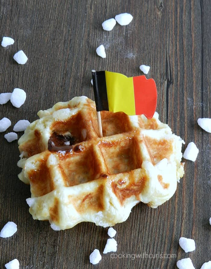 A Chocolate stuffed Liege waffle surrounded by pearl sugar with a Belgian flag stick in the middle.