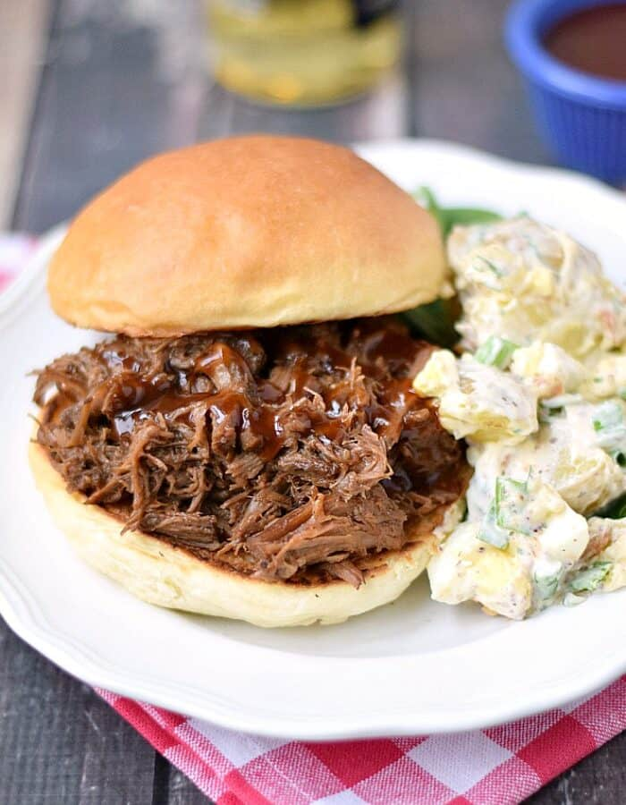 barbecue beef sandwich with a side of potato salad on a white plate that is sitting on a red and white check napkin