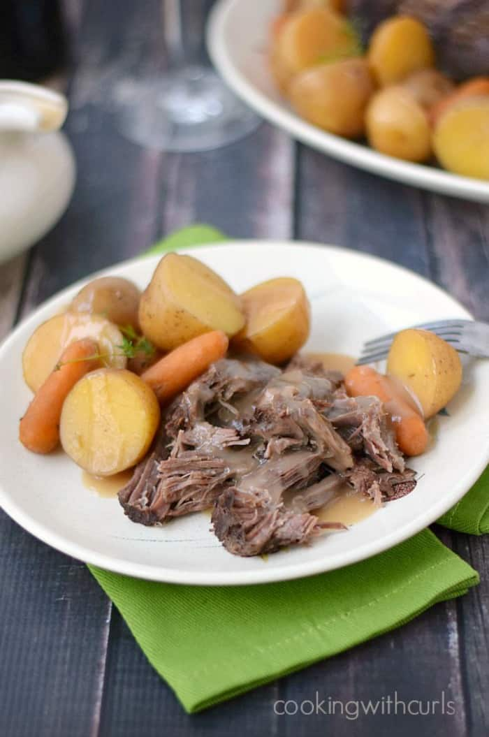sliced pot roast, vegetables and gravy on a white plate sitting on a green napkin with another plate of pot roast in the background