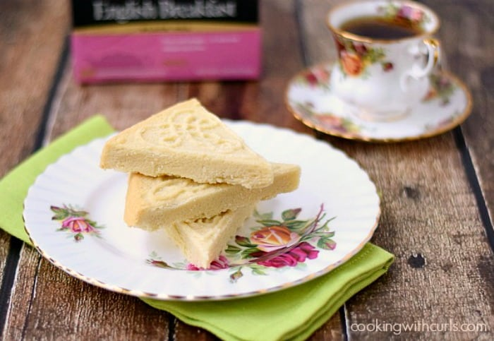 traditional shortbread on a plate sitting beside a cup of tea and a box of english breakfast tea