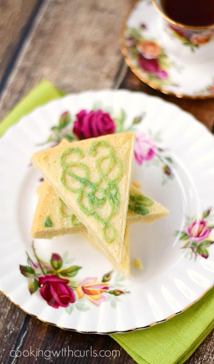 Traditional Shortbread on a plate decorated with roses sitting beside a cup of tea