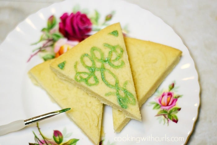 Traditional Shortbread painted with edible glitter sitting on a rose decorated plate