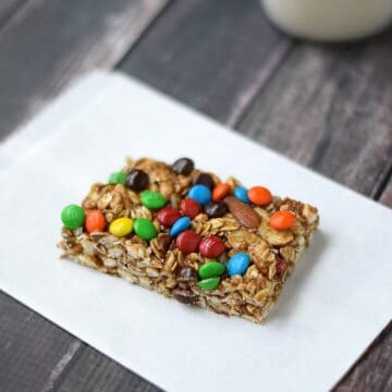 M&M's Almond Granola Bars on a white napkin with a glass of milk in the upper corner.