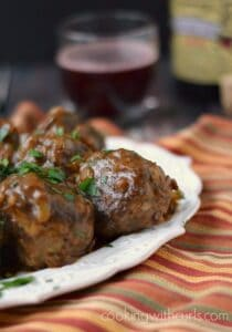 meatballs on a white platter sitting on a fall colored napkin