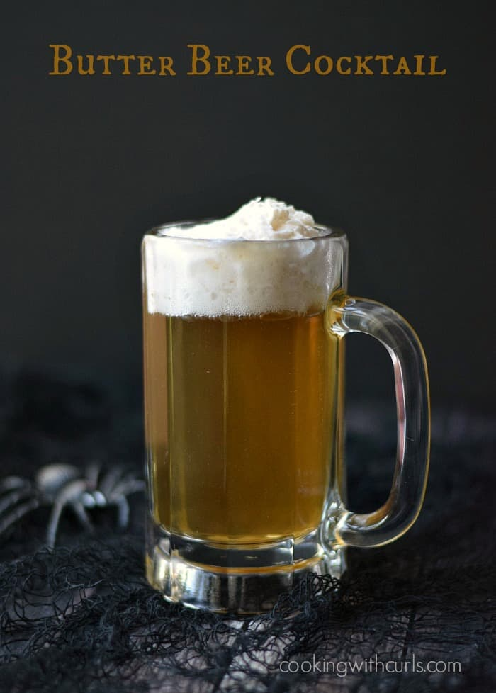 butter beer cocktail in a glass mug sitting on a black net covered board with a black spider on the left side