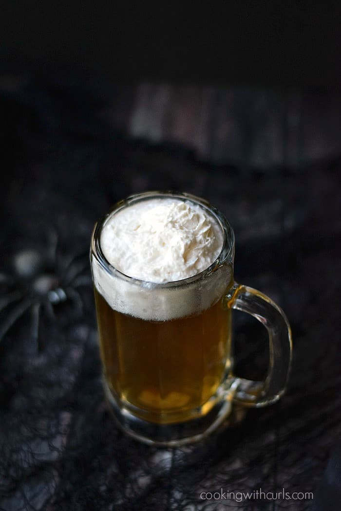 butter beer cocktail in a glass mug sitting on a black net covered table with a large black spider on the left side