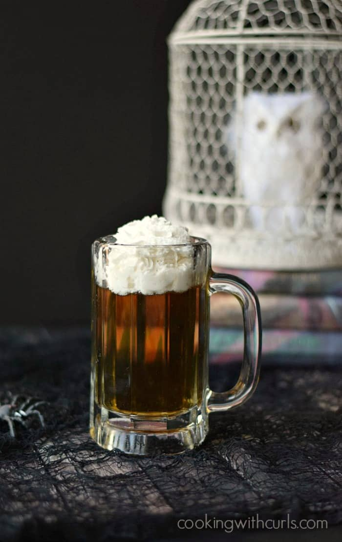 butter beer cocktail in a glass mug in front of a stack of harry potter books topped with a white owl in a white cage
