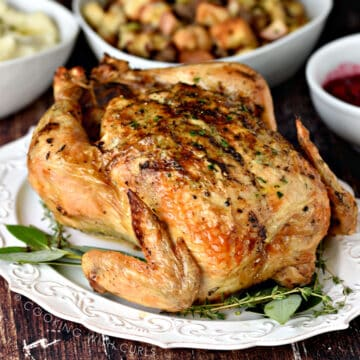 A whole roast chicken on a white platter with bay leaves and thyme with bowls of stuffing and mashed potatoes in the background.