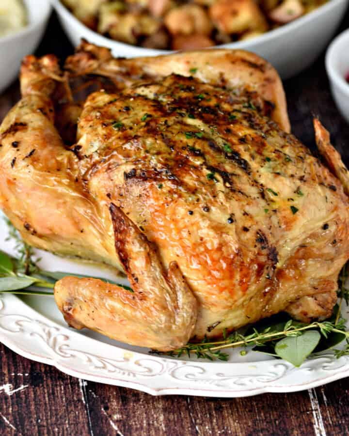 A whole roast chicken on a white platter with bay leaves and thyme.
