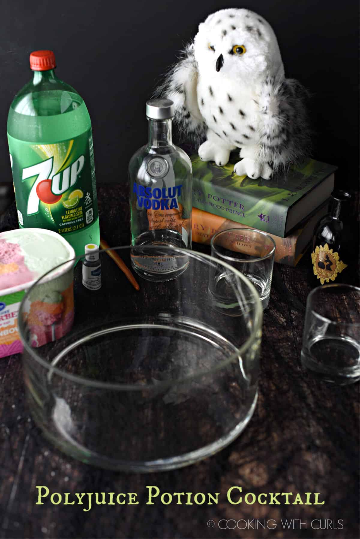 polyjuice potion ingredients; glass punch bowl, rainbow sherbet, 7up, Absolut vodka, lime green food coloring and a stack of harry potter books with a stuffed Hedwig owl on top.