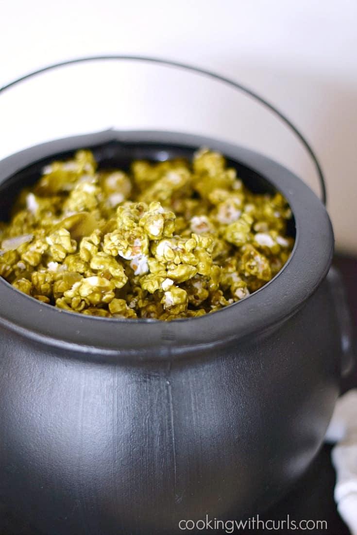 A black cauldron filled with dark green Troll Boogers popcorn