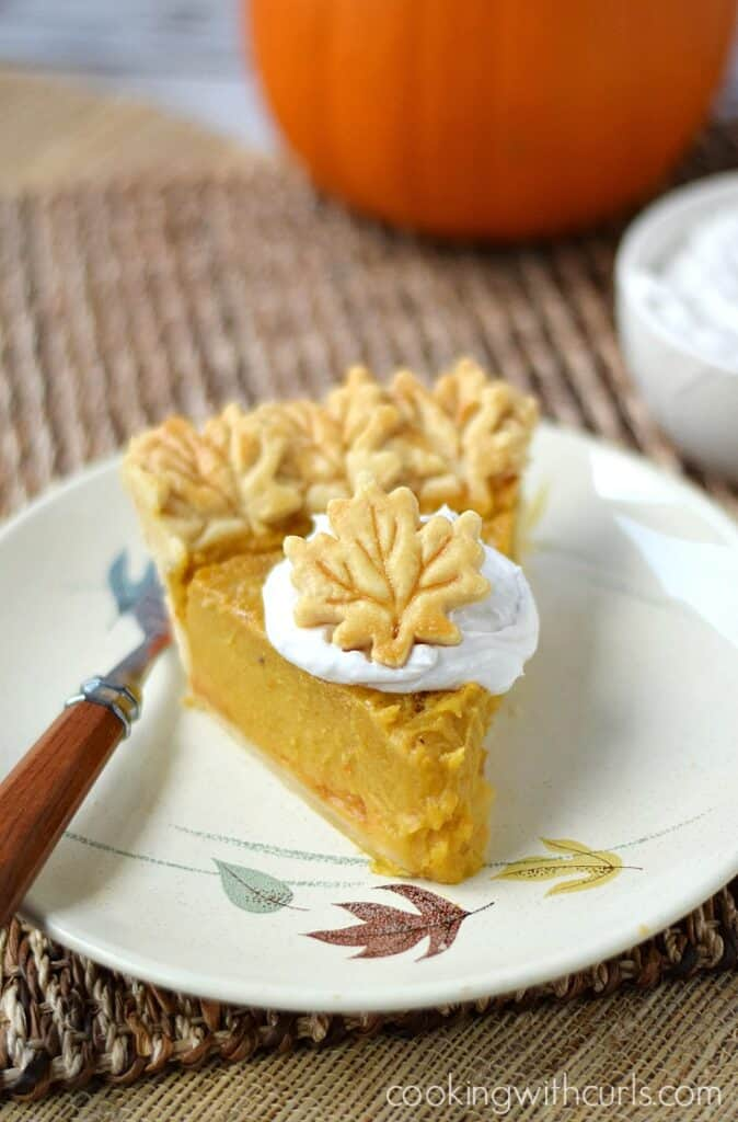A slice of delicious Dairy-free Pumpkin Pie topped with coconut whipped cream | cookingwithcurls.com