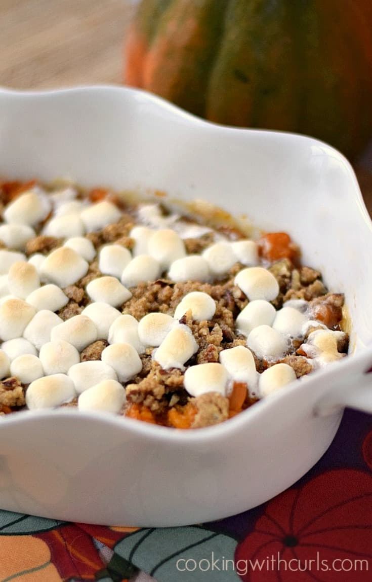 Candied Sweet Potatoes topped with streusel and min marshmallows in a white casserole dish