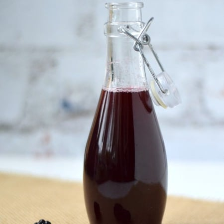 clear glass bottle filled with blackberry simple syrup sitting in front of a white brick wall with fresh blackberries laying in front