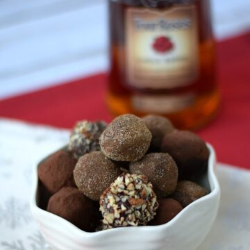 Chocolate Bourbon Truffles with a bottle of Four Roses Bourbon in the background.