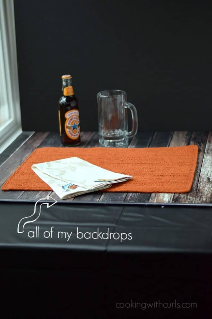 backdrop on table with an orange place mat, bottle of beer, empty glass mug and a black board as a back drop
