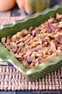 Bacon Pecan Stuffing in a green casserole dish with pumpkins in the background