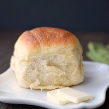 a dinner roll sitting on a small, white plate with two pats of butter