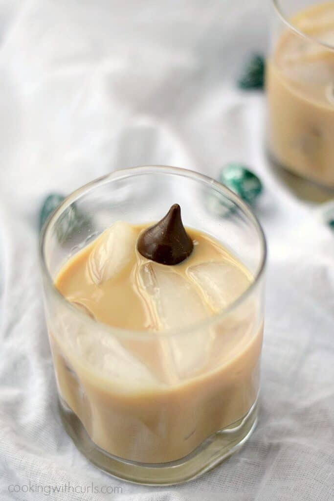 peppermint kiss cocktail with ice cubes in a small, square glass with a kiss floating on top
