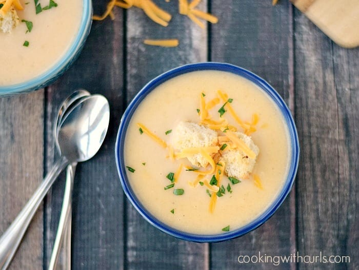 two blue bowls filled with potato cheese soup sitting on a wooden board with two spoons