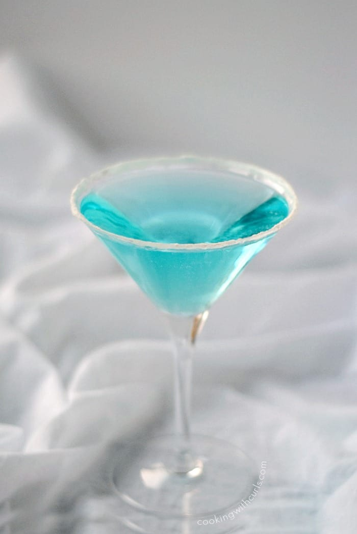 clear blue cocktail in a martini glass with a sugar coated rim