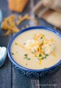 a dark blue bowl filled with potato cheese soup, and topped with croutons and shredded cheddar cheese with additional cheese in the background