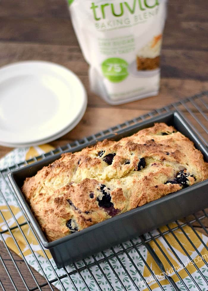 lemon blackberry bread in a metal loaf pan sitting on a wire rack with white plates to the left and a bag of Truvia to the right