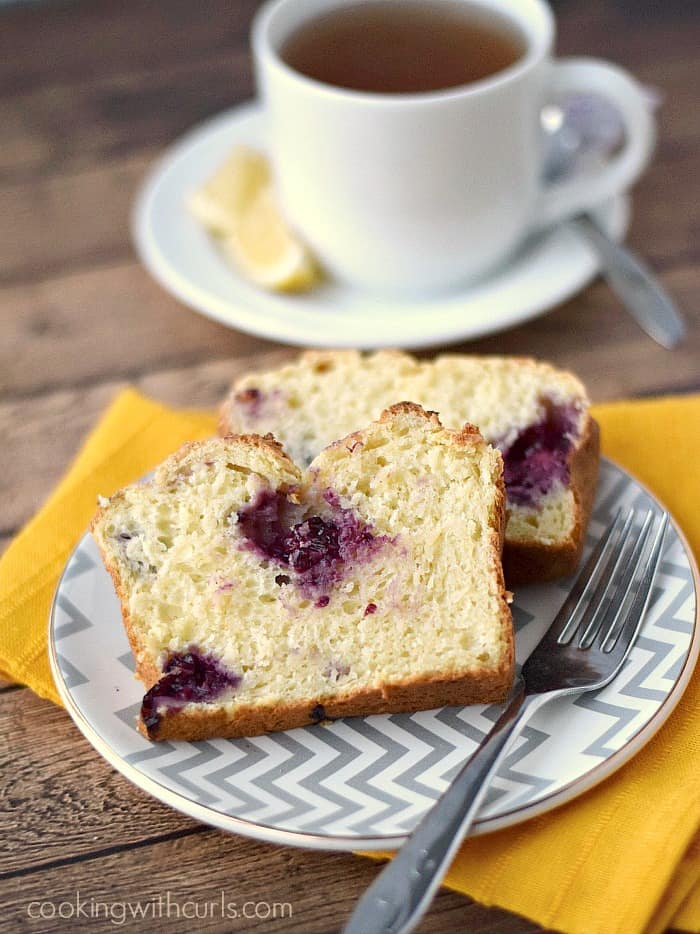 two slices of lemon blackberry bread on a gray and white zigzag patterned plate, sitting on a yellow napkin with a cup of tea in the background