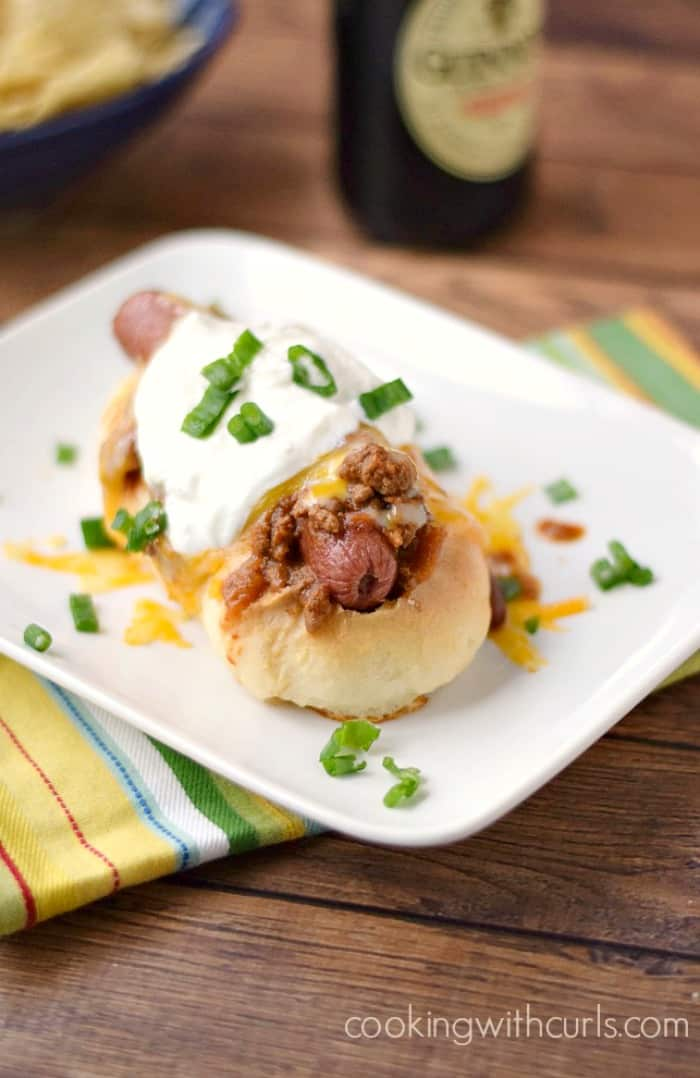a hot dog smothered in chili and melted cheese, topped with sour cream and sliced green onions sitting on a white plate with a bottle of Guinness in the background