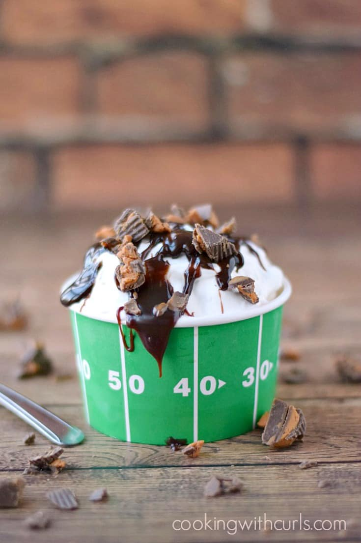 Touchdown Sundae Ice Cream Pie in a green football cup surrounded by broken candy pieces