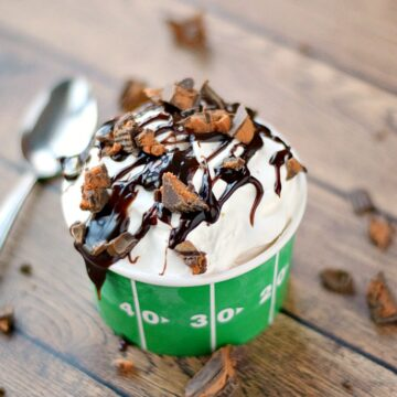 Touchdown Sundae Ice Cream Pie in a green football cup surrounded by broken Resse's peanut butter cups