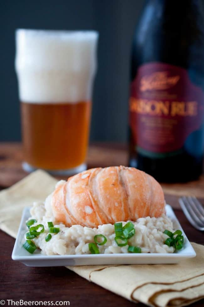Beer-and-Butter-Poached-Lobster-with-Saison-Risotto on a square white plate.