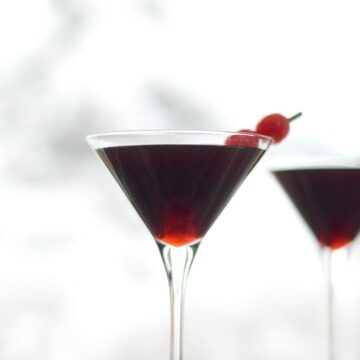 Cherry Cheesecake Martinis sitting in front of a snowy window