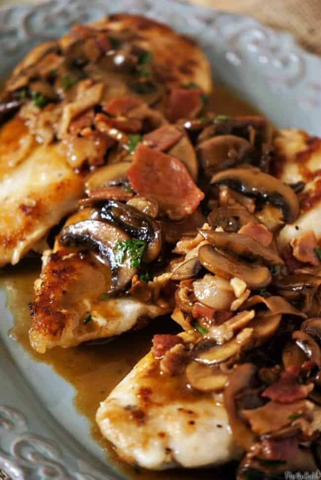 Sliced mushrooms topped Chicken marsala on a gray plate.