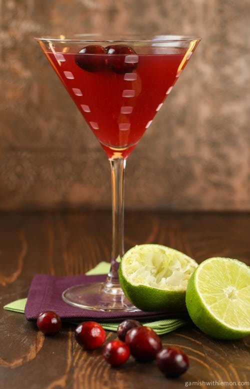 A Cranberry Gimlet in a martini glass with two cherries floating on top and  lime halves sitting at the base.