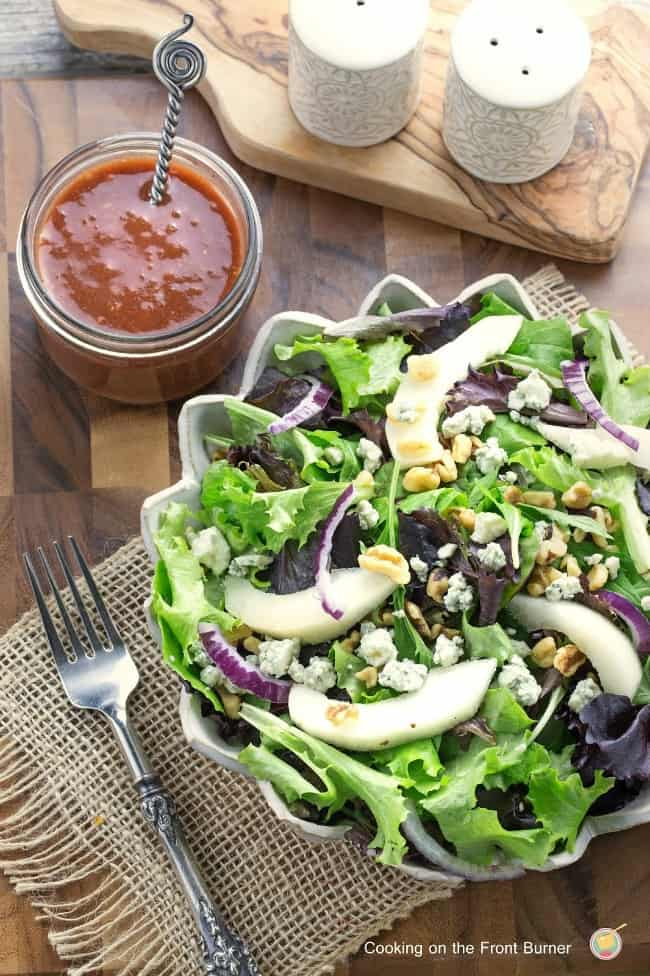 Pear-and-Walnut-Salad-with-Cranberry-Vinaigrette in a scalloped bowl with a jar of sauce on the side.