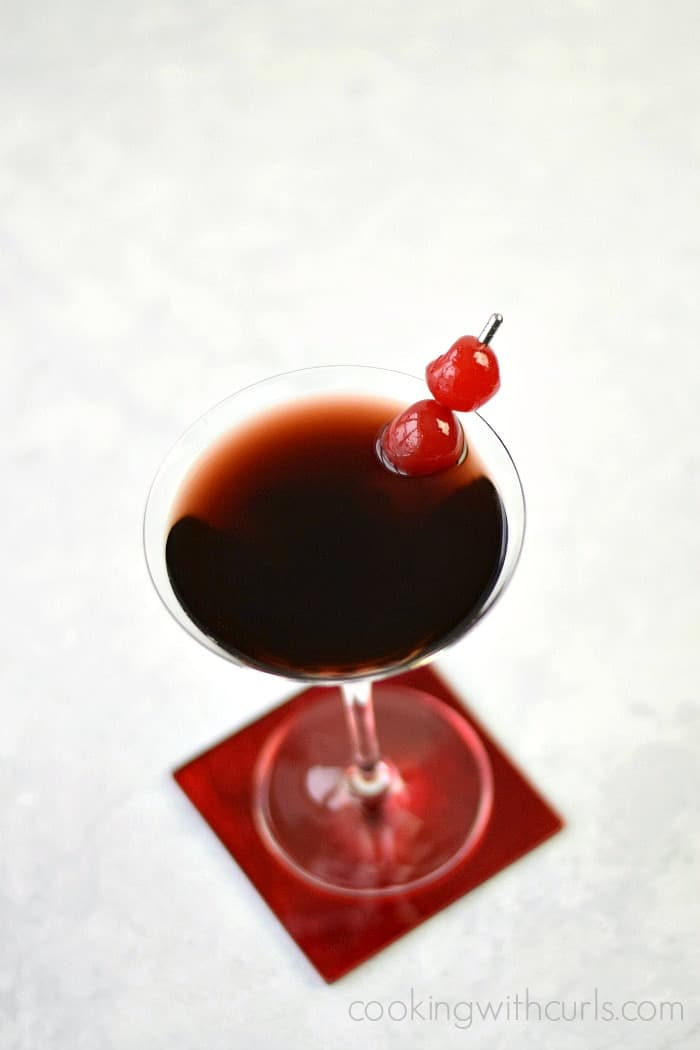 deep red cherry cheesecake martini in a martini glass sitting on a red coaster with cherries as a garnish