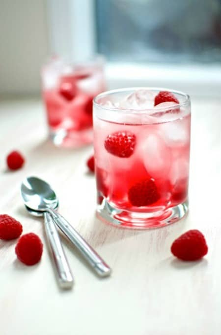 Two cran-raspsberry spritzers in short glasses sitting next to two spoons and scattered fresh raspberries.