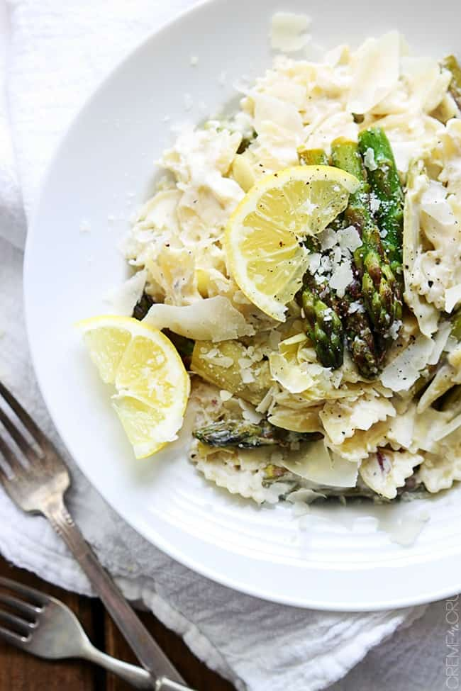 lemon-asparagus-artichoke-pasta topped with Parmesan cheese on a white plate.