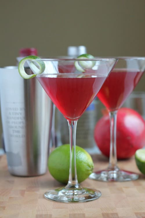 two pink pomegranate cosmopolitans  garnished with a lime peel swirl in martini glasses.