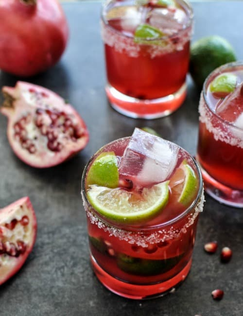 Two pomegranate margaritas with salt rimmed glasses garnished with lime wedges and surrounded by split pomegranates.