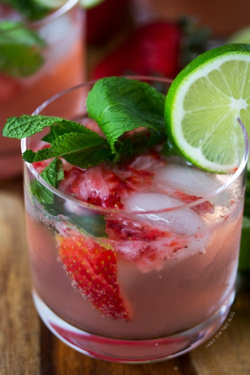 Two strawberry mojitos garnished with lime wheels and fresh mint leaves.