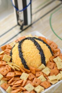 bacon cheddar cheeseball covered in shredded cheddar cheese and minced olives designed to look like a basketball sitting on a white plate surrounded by crackers